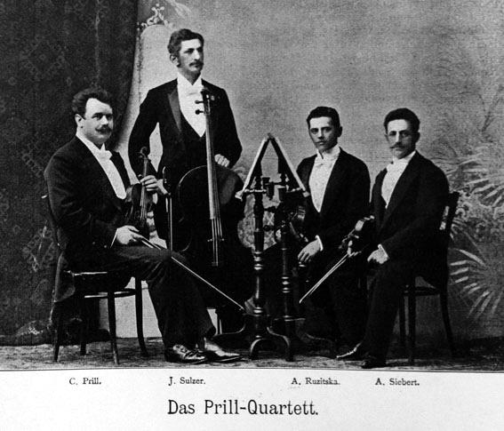Black and white photograph of the Prill Quartet, three members seated, the cellist standing
